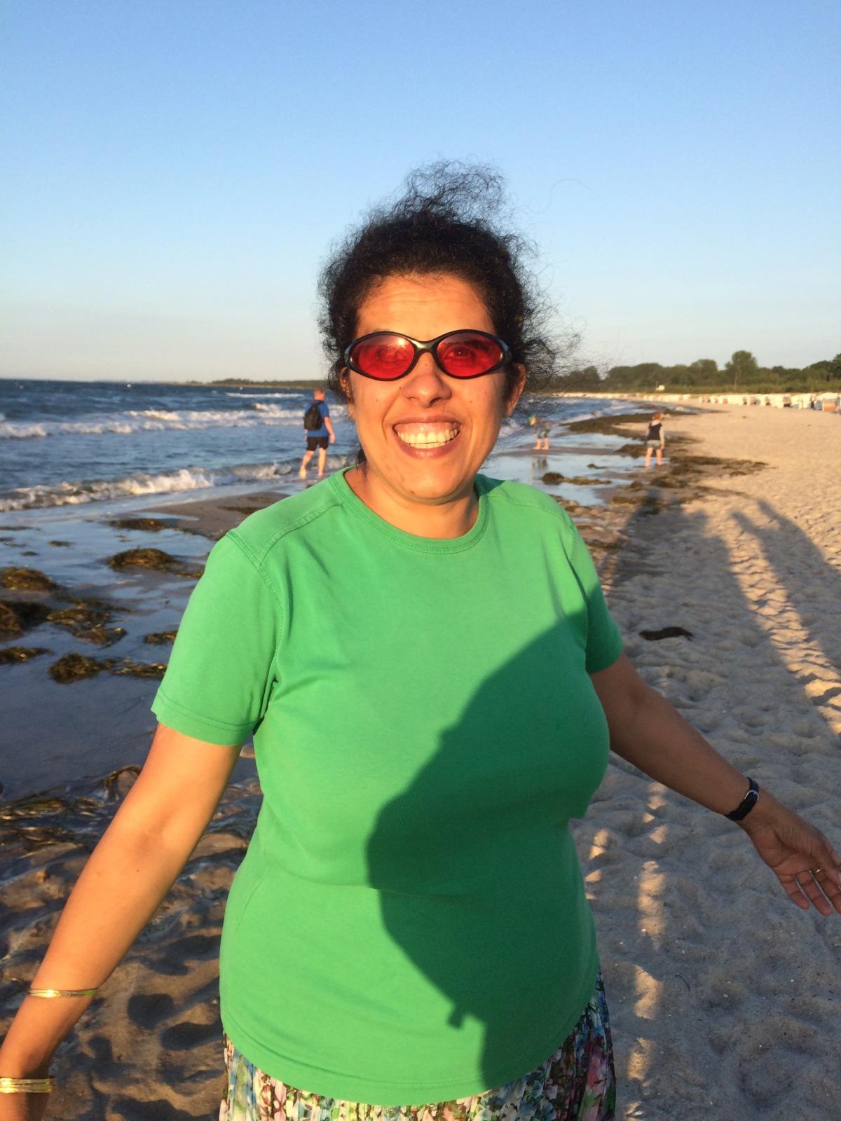 Lydia am Strand mit grünem T-Shirt und buntem Rock