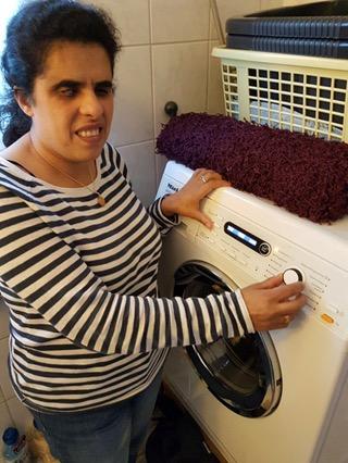 Lydia vor einer Waschmaschine mit heller Anzeige auf dunklem Hintergrund.