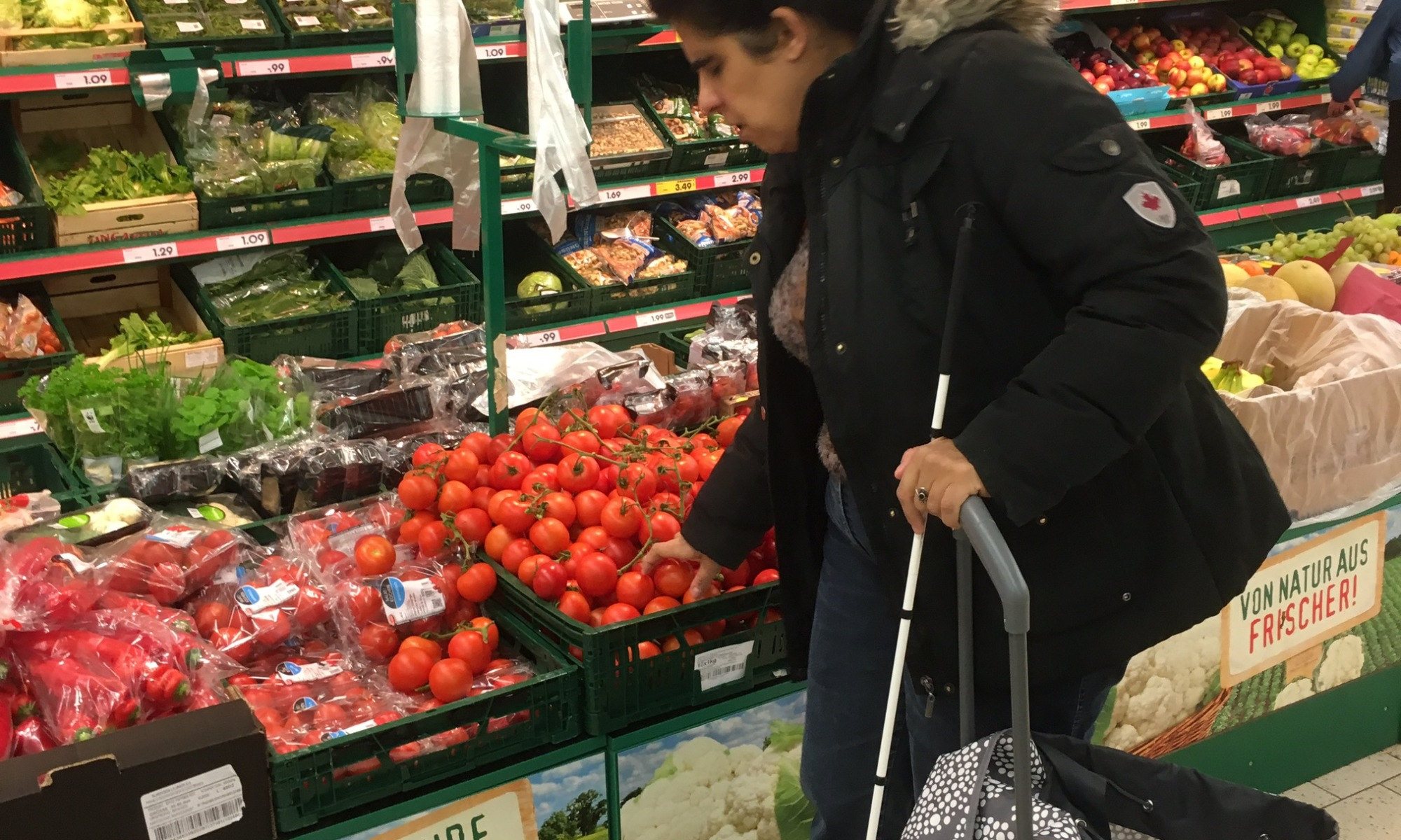Lydia mit Blindenstock und Shopper am Obststand eines Supermarktes.