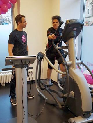 Lydia auf dem Crosstrainer, neben ihr steht Christian.