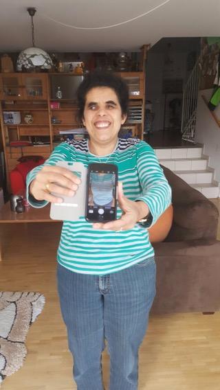 Lydia mit einem iPhone, dessen Kamera auf ihr Oberteil gerichtet ist.