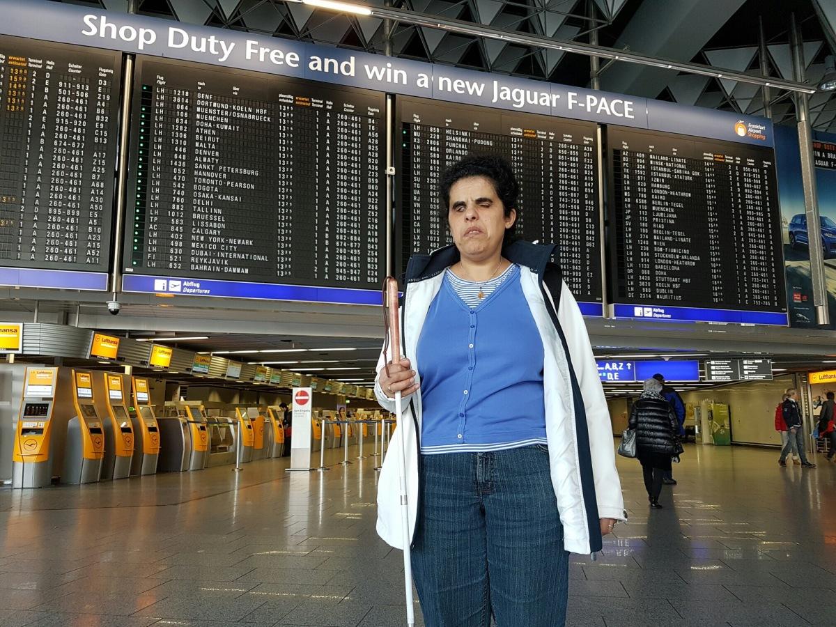 Lydia am Flughafen. Im Hintergrund ist eine Anzeigetafel.