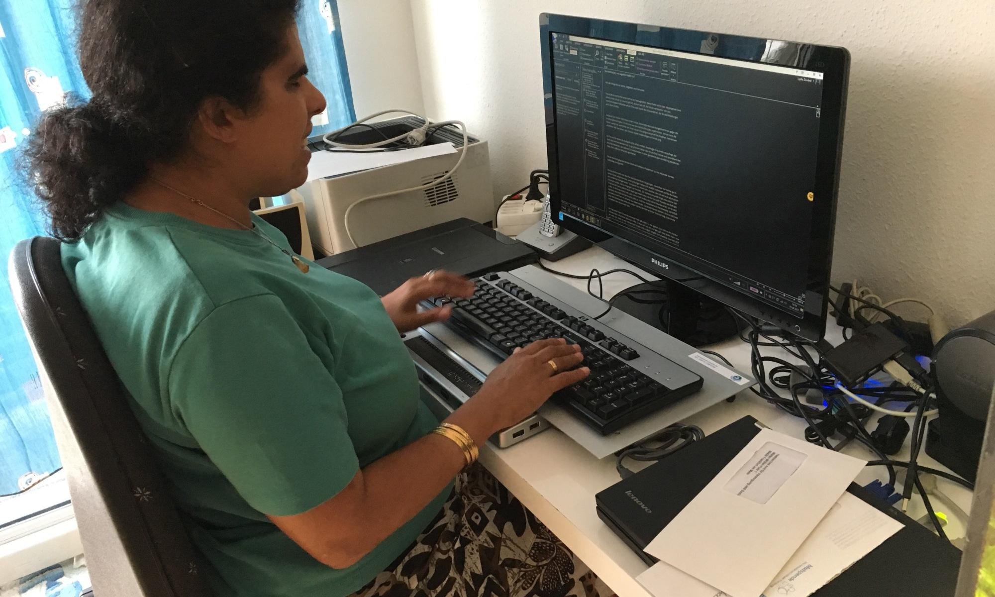 Lydia sitzt am Schreibtisch, auf dem ein Computerarbeitsplatz steht.