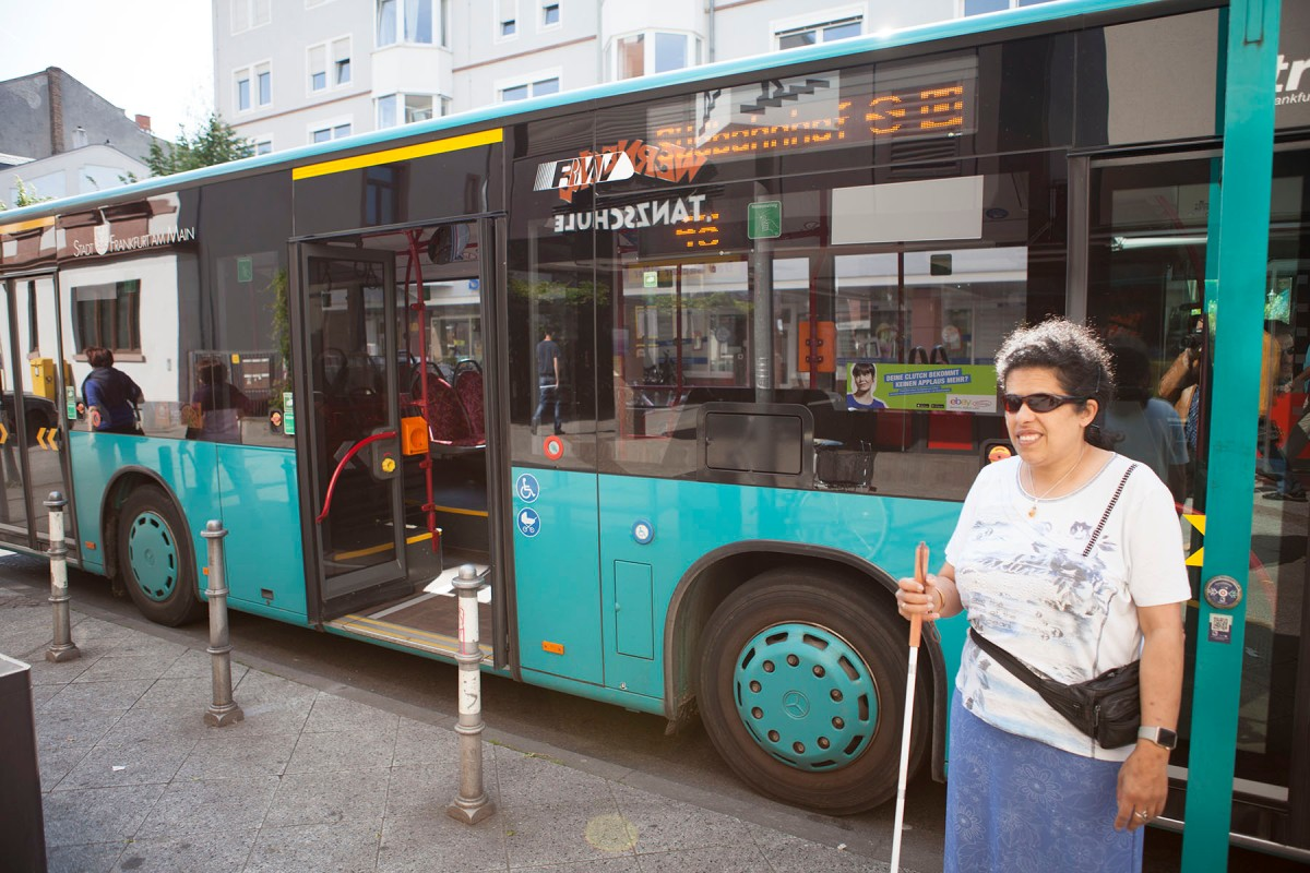 Lydia steht an einer Bushaltestelle