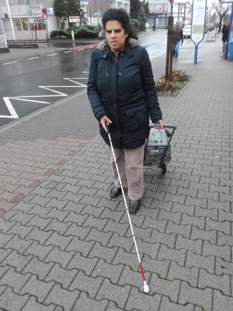 Lydia läuft mit Blindenstock und Shopper eine Straße entlang