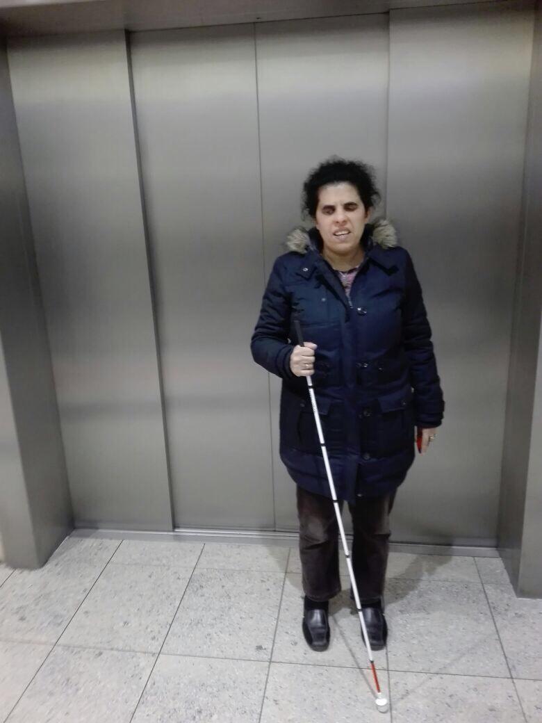 Lydia mit Stock vor einem Aufzug