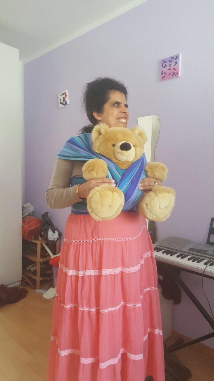 Lydia trägt einen Teddy in einem Tragetuch.