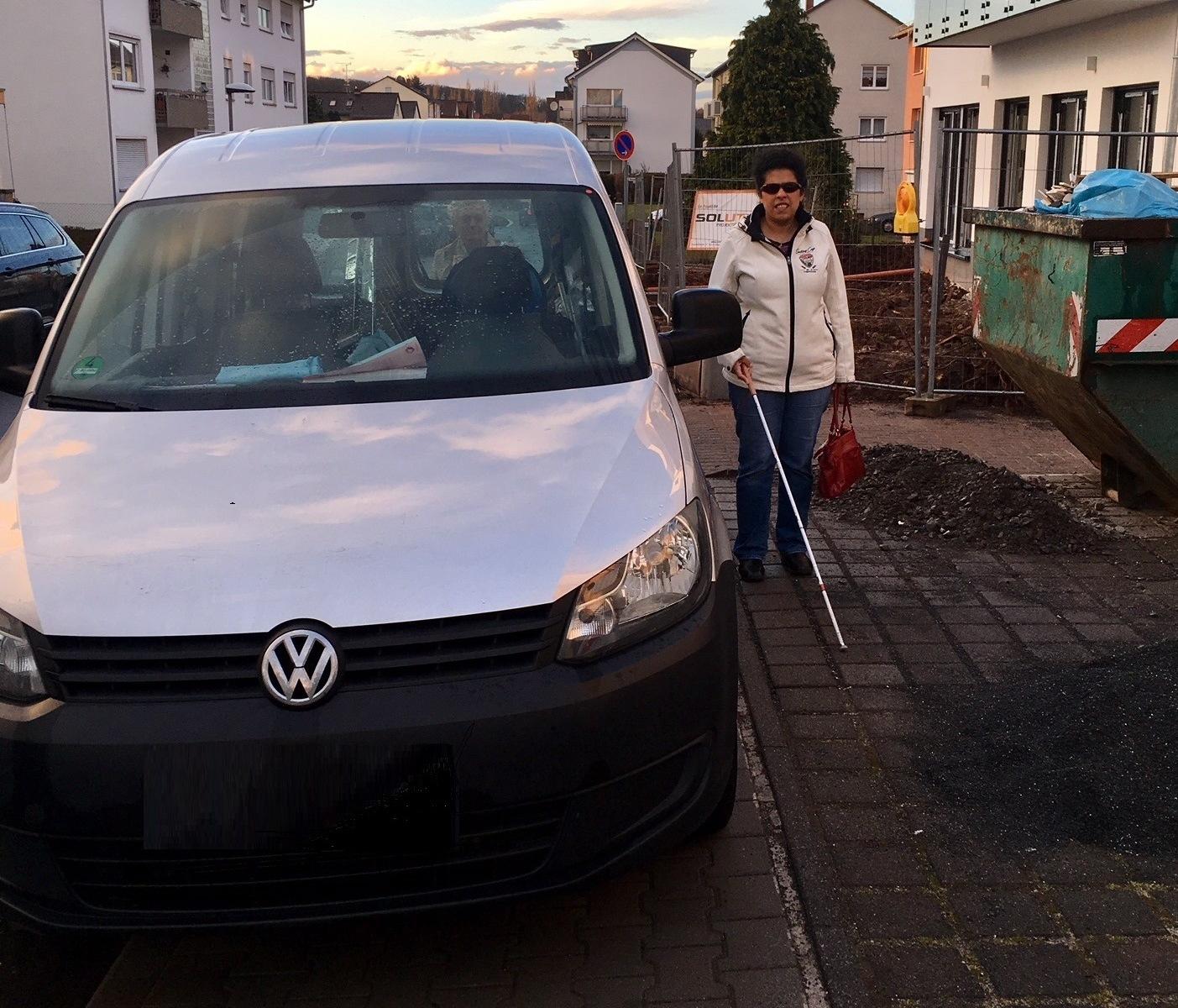 Lydia läuft mit Blindenstock an einem zu eng parkendem Auto entlang.