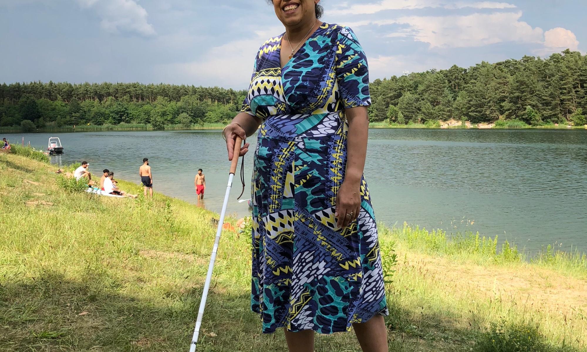 Lydia läuft lächelnd mit Blindenstock an einem See entlang.