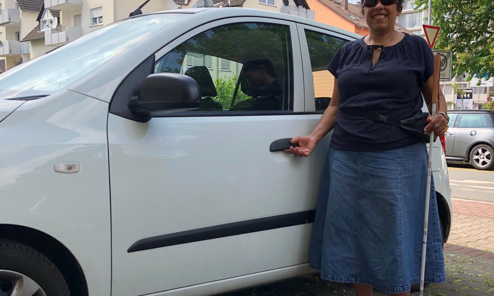Lydia steht neben der Fahrertür eines Autos.