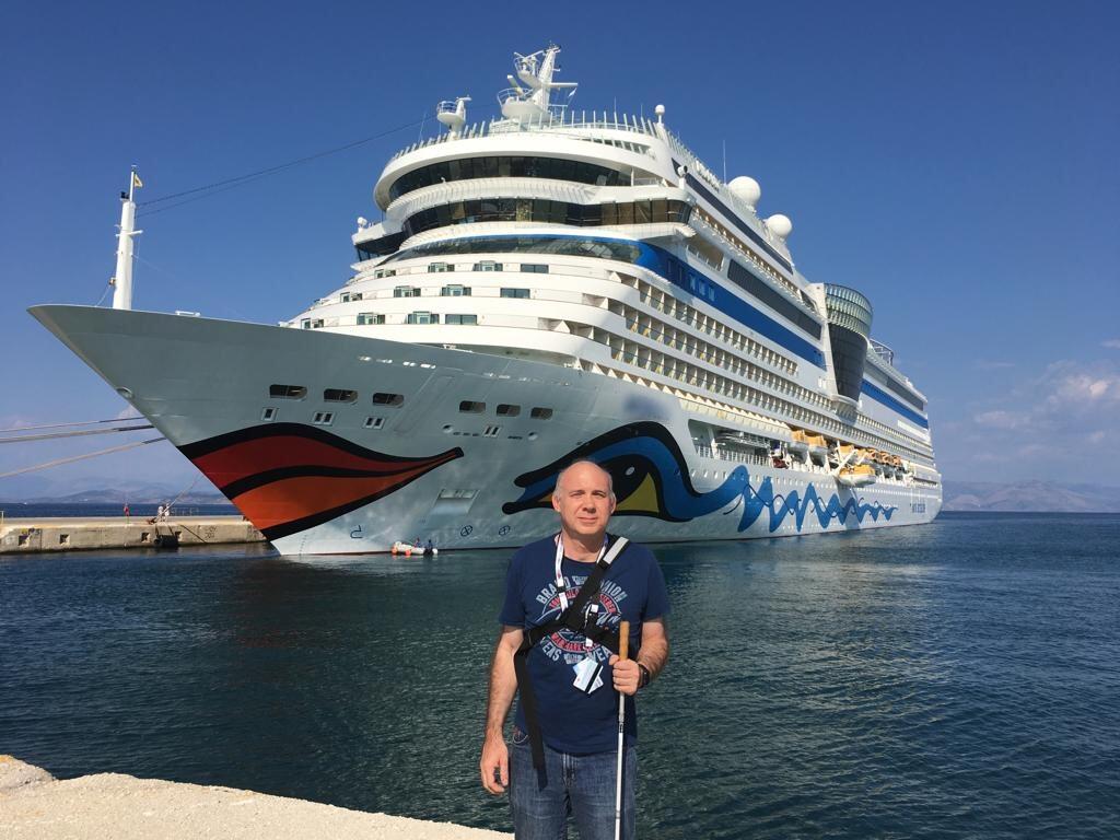 Ein blinder Mann mit Kreuzfahrtschiff im Hintergrund