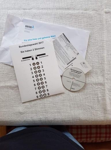 Wahlbenachrichtigung, Wahlschablone der BTW 2017 und Info-CD des BBSB liegen auf einem Tisch