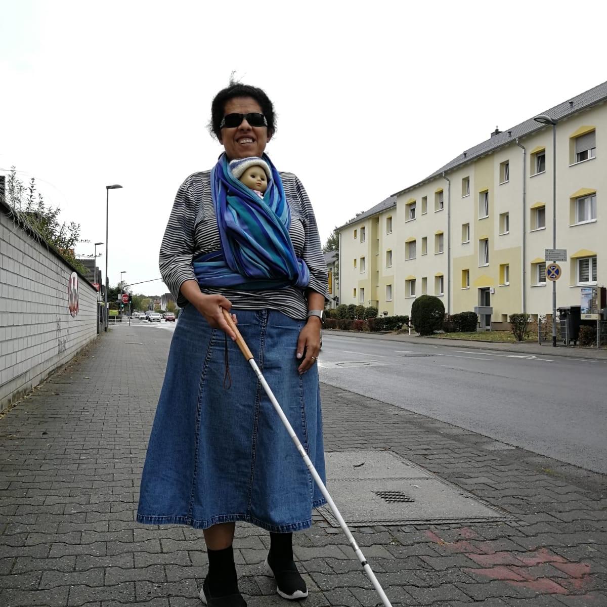 Lydia läuft mit Puppe im Tragetuch und Blindenstock eine Straße entlang.