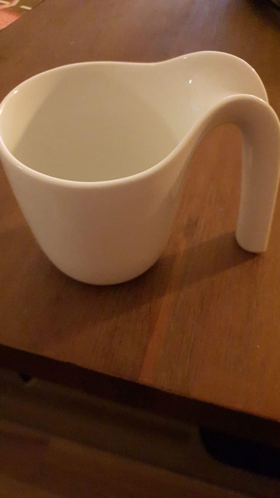 Eine helle Tasse steht auf dunklem Untergrund