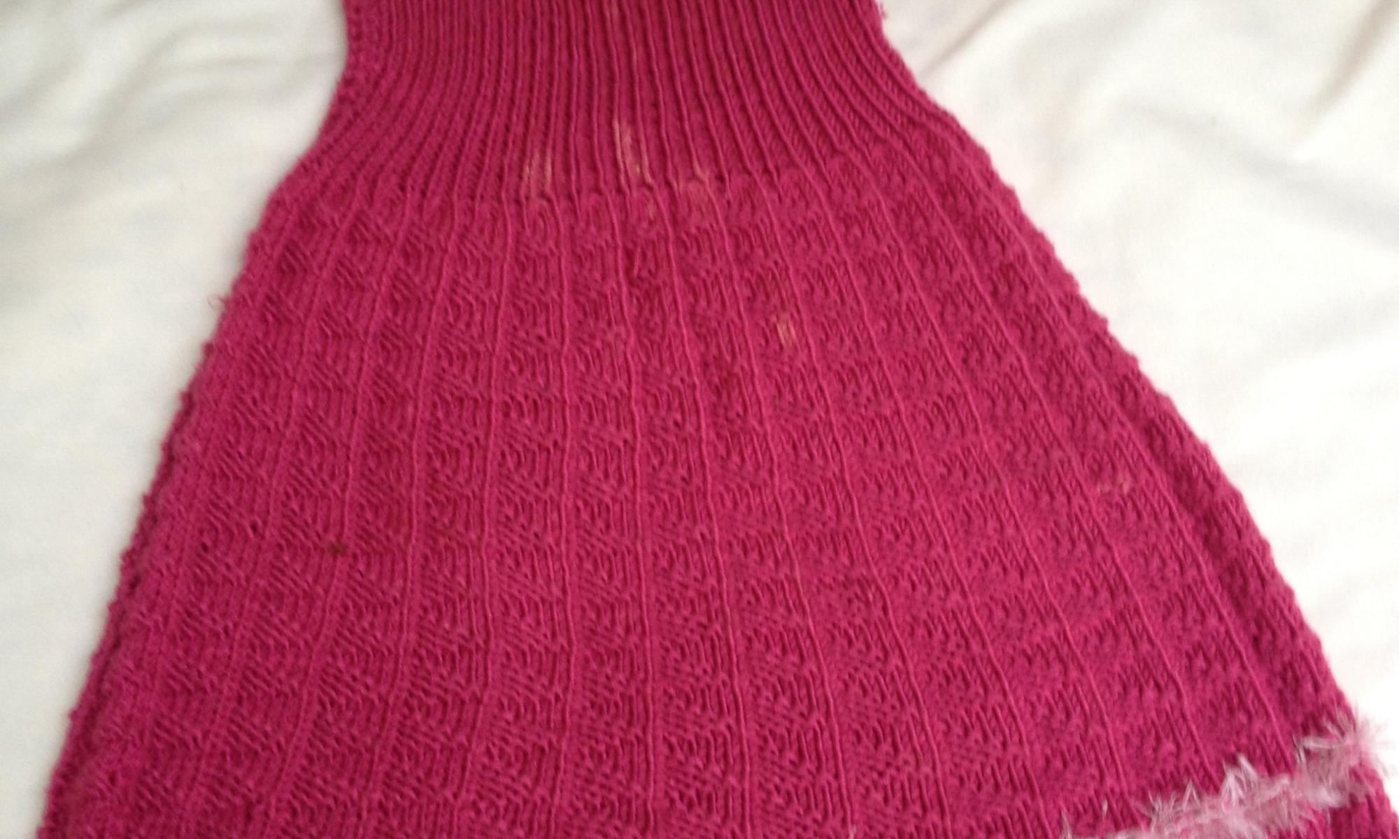 Ärmelloses Strickkleid mit V-Ausschnitt, dass mit Fransengarn verziert ist. Die untere Kleidhälfte besteht aus Messerspitzenmuster und 2 Streifen Fransengarn.