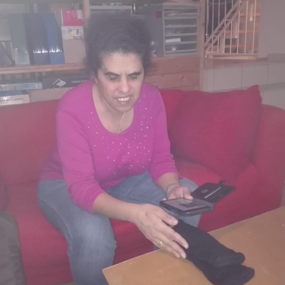 Lydia richtet ein Smartphone auf einen schwarzen Handschuh.
