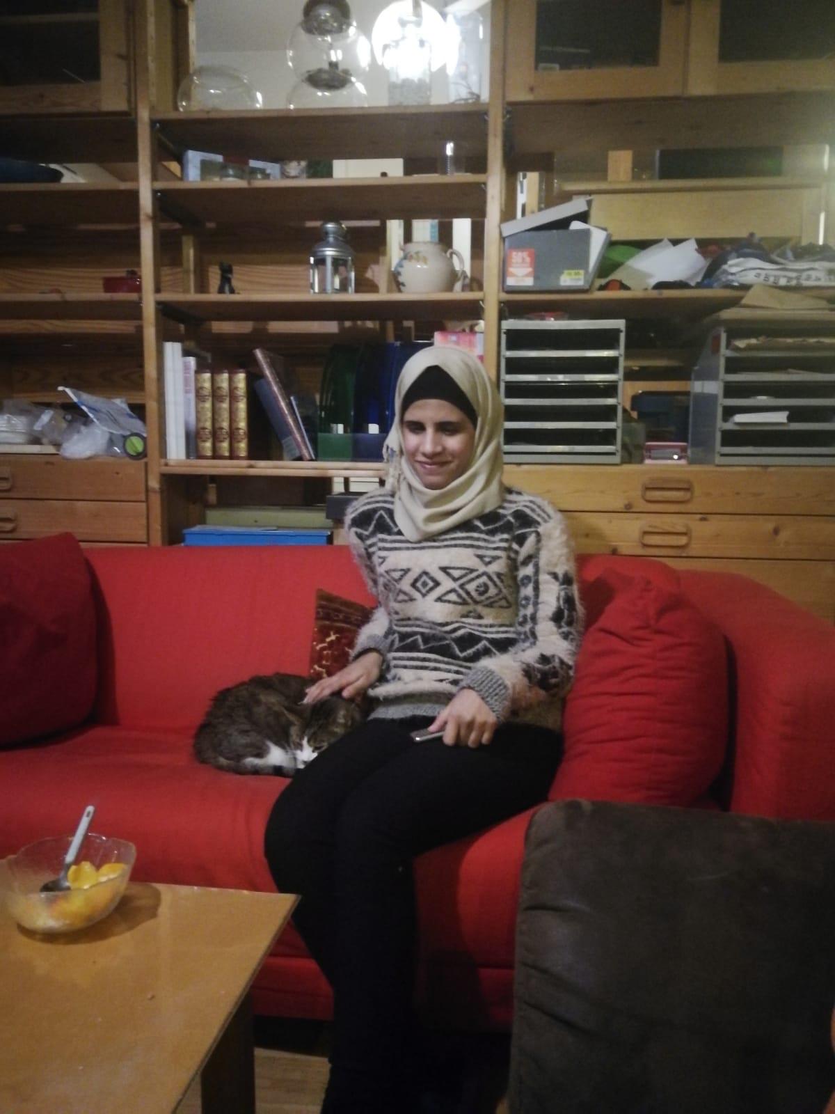 Amal sitzt auf einer roten Couch und streichelt mit der rechten Hand Katze Mignones kopf