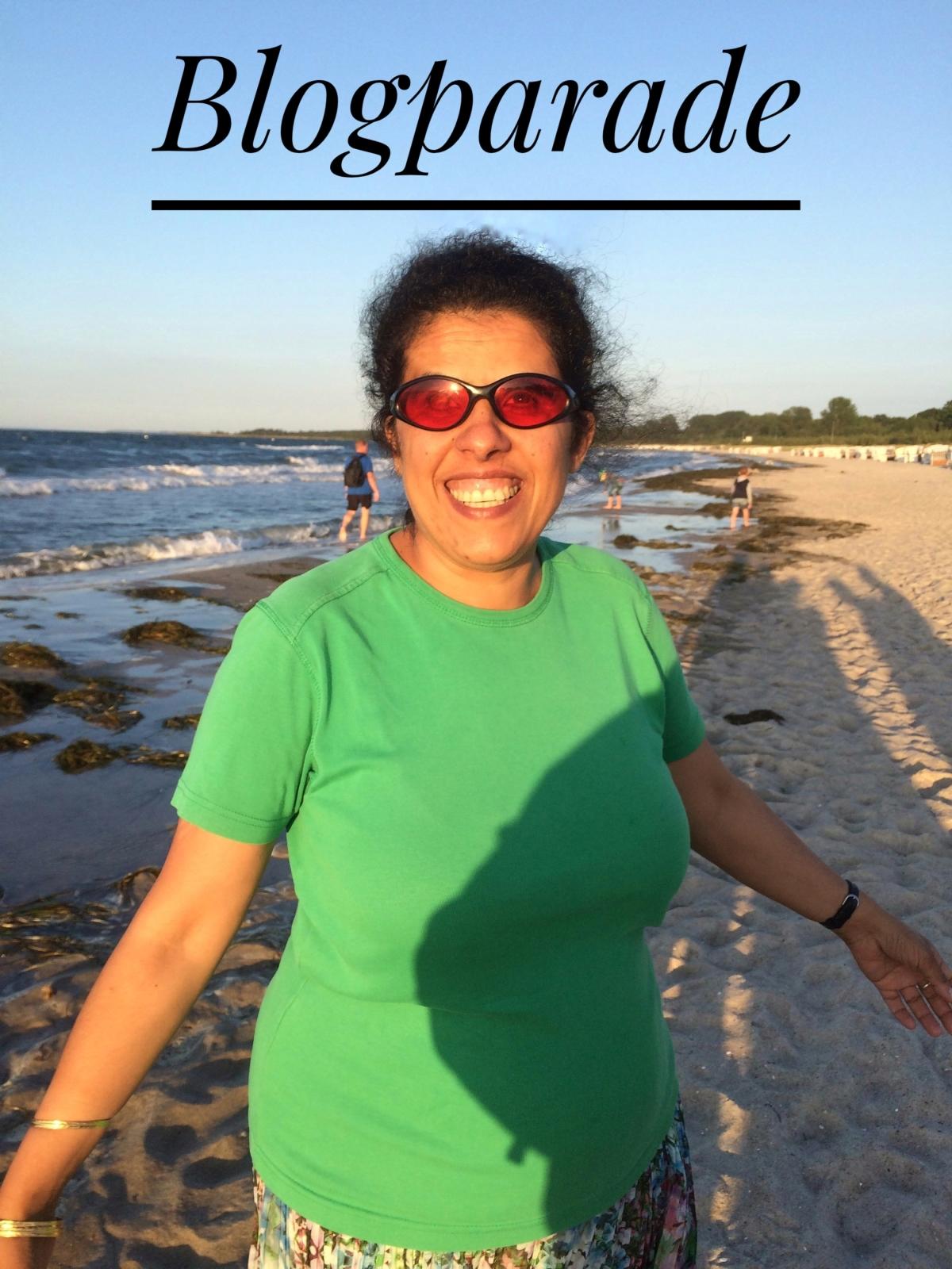 """Lydia steht lächelnd am Strand. Über ihrem Kopf steht der Schriftzug """"Blogparade"""""""