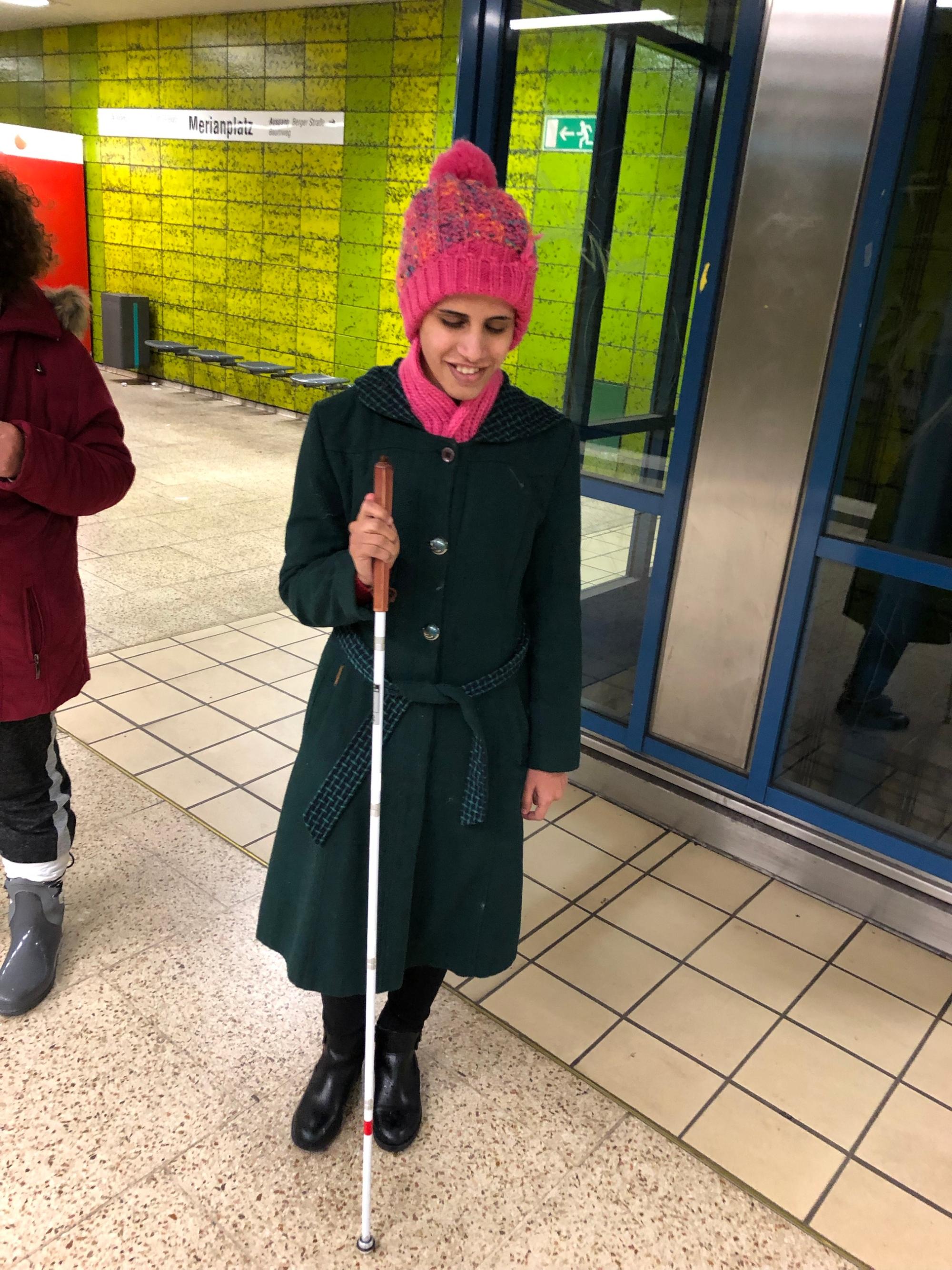 Amal vor einem Aufzug an einer U-Bahn-Station