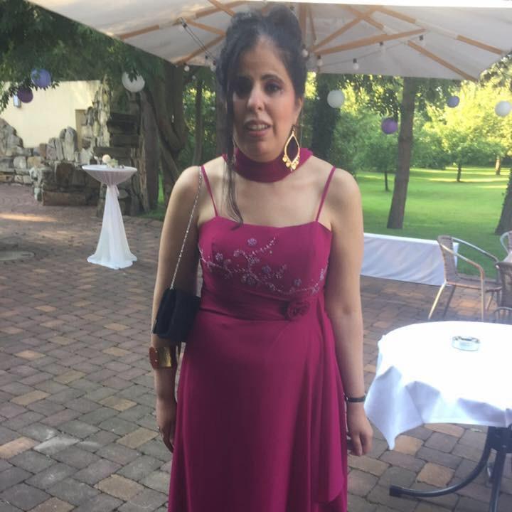 Amy Zayed steht im roten Kleid auf einer Terasse.