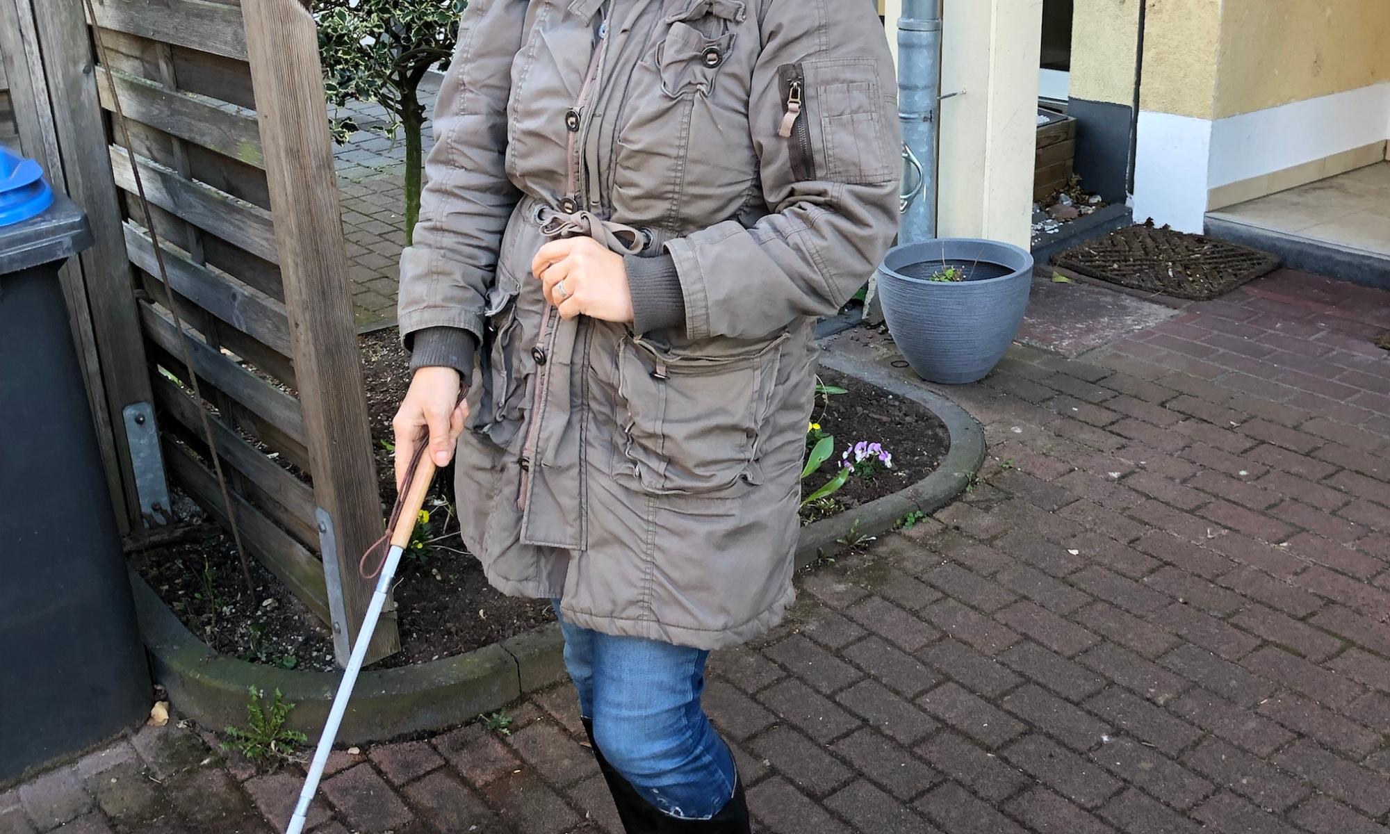 Eine Frau mit verbundenen Augen hält einen Blindenstock in der rechten Hand.