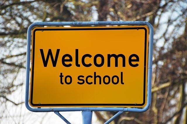 """Ein gelbes Straßenschild mit der Aufschrift """"welcome to school"""""""
