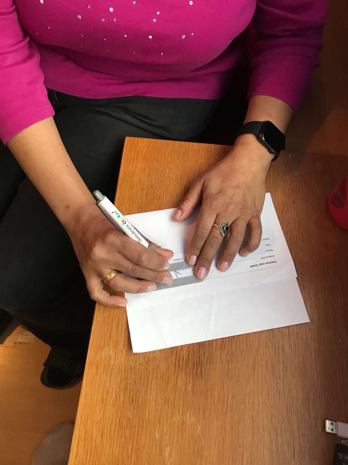 Lydia hält mit der linken Hand eine Unterschriftenschablone fest, während sie mit der Rechten darin unterschreibt