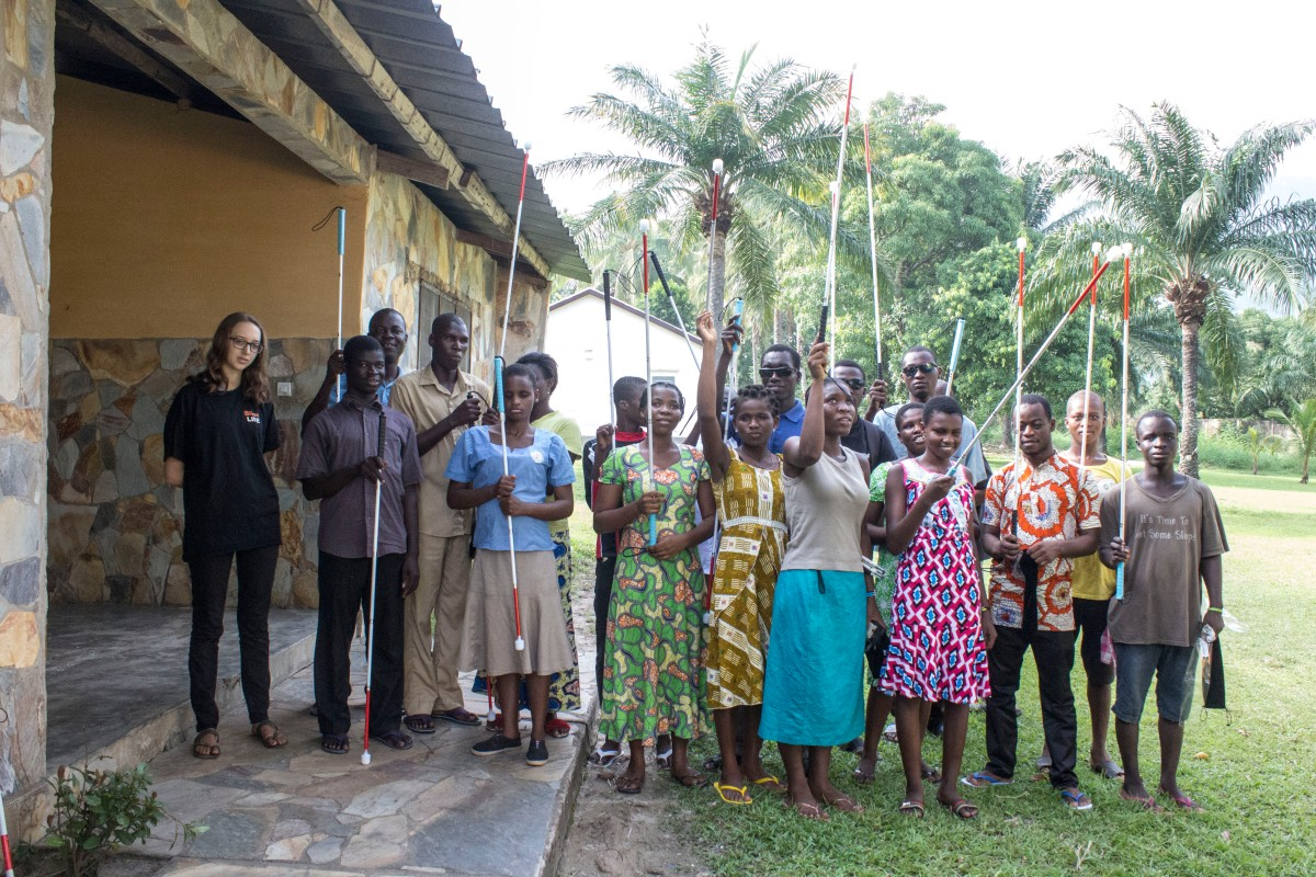 Jasmin mit blinden Schülern aus Togo, die Blindenstöcke in die Höhe halten