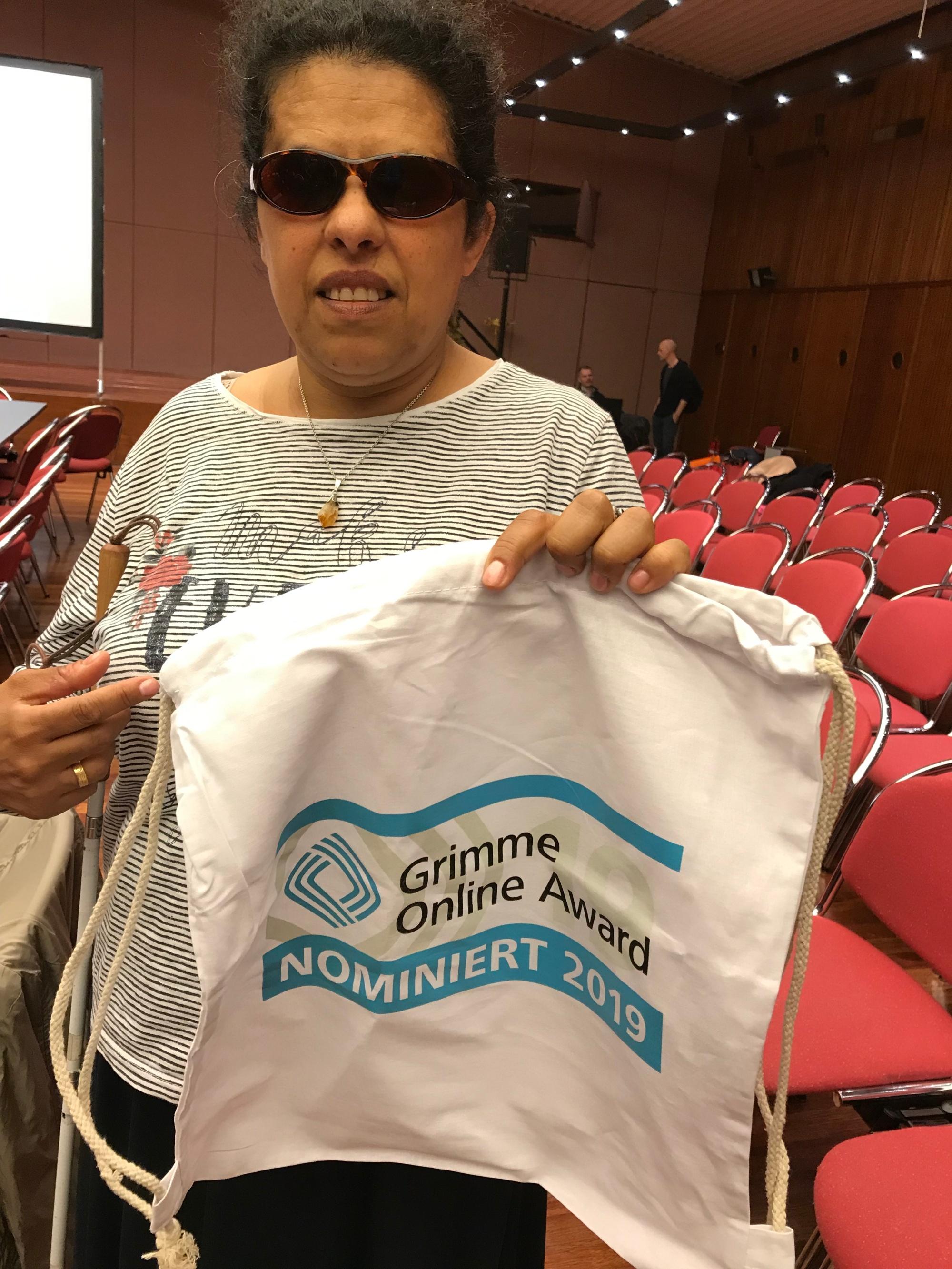 Lydia hält eine Stofftasche, mit Aufdruck nominiert für Grimme Online Award 2019
