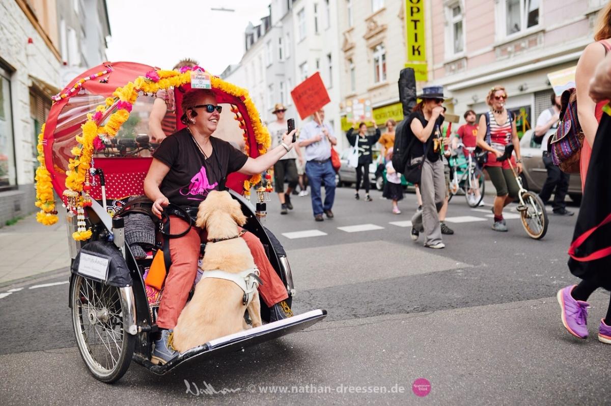 Andrea Eberl lächelnd mit Blindenführhund in einer Fahrradrikscha