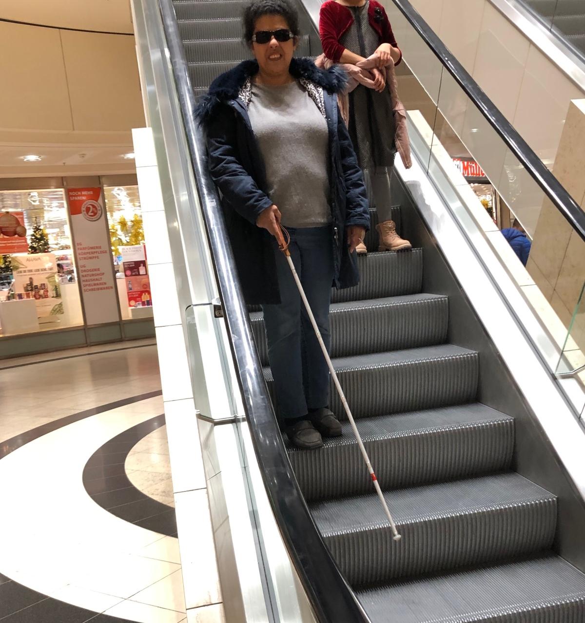 Lydia steht auf einer Rolltreppe abwärts