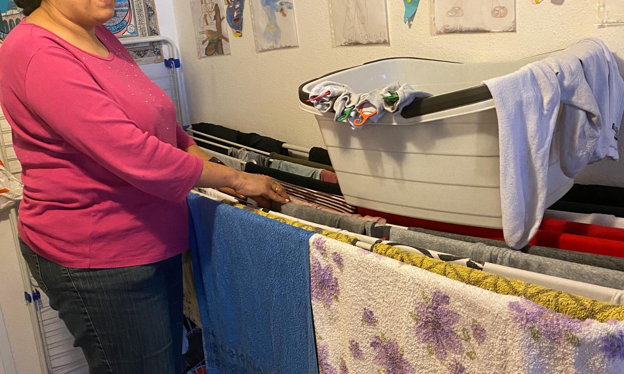 Lydia steht an einem vollen Wäscheständer, auf dem ein Korb mit Socken steht.