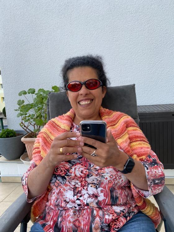 Lydia sitzt mit iPhone in einem Gartensessel auf der Terrasse.