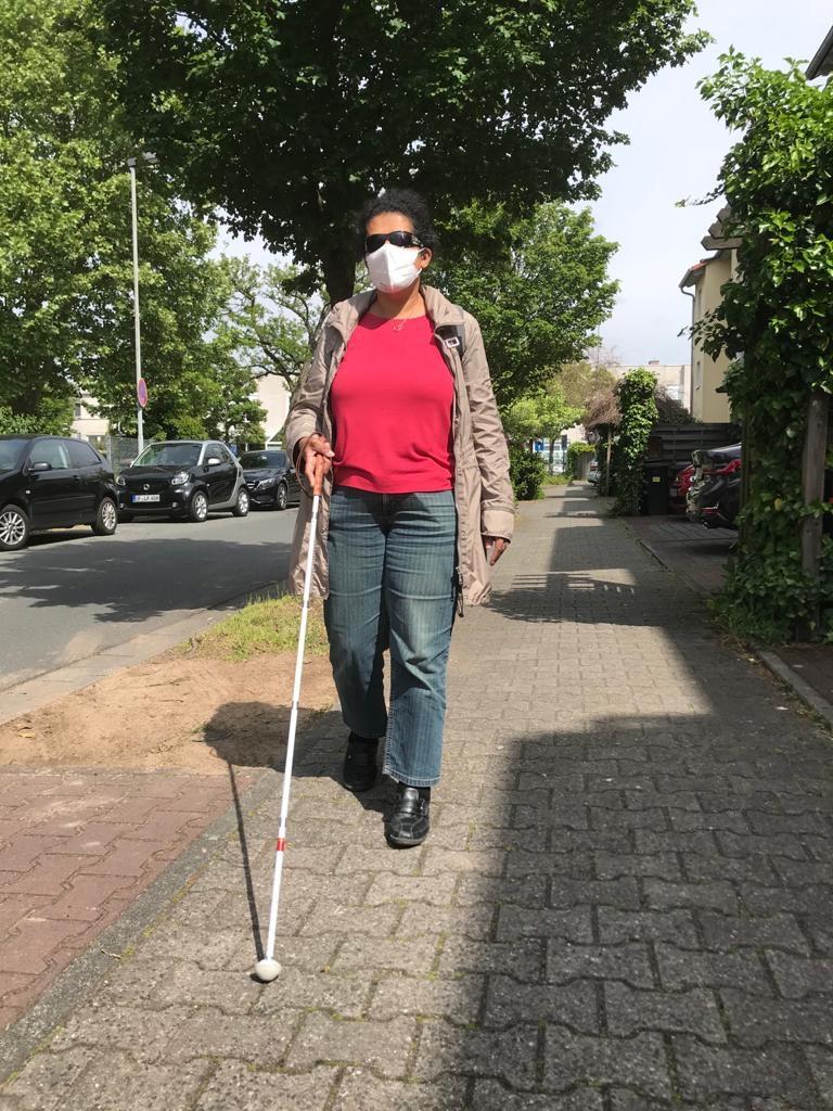 Lydia läuft mit Stock und Maske eine Straße entlang.