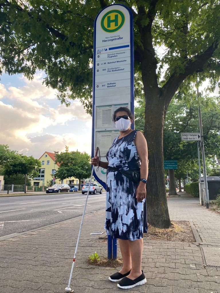 Lydia steht mit Maske und Blindenlangstock an einer Bushaltestelle.