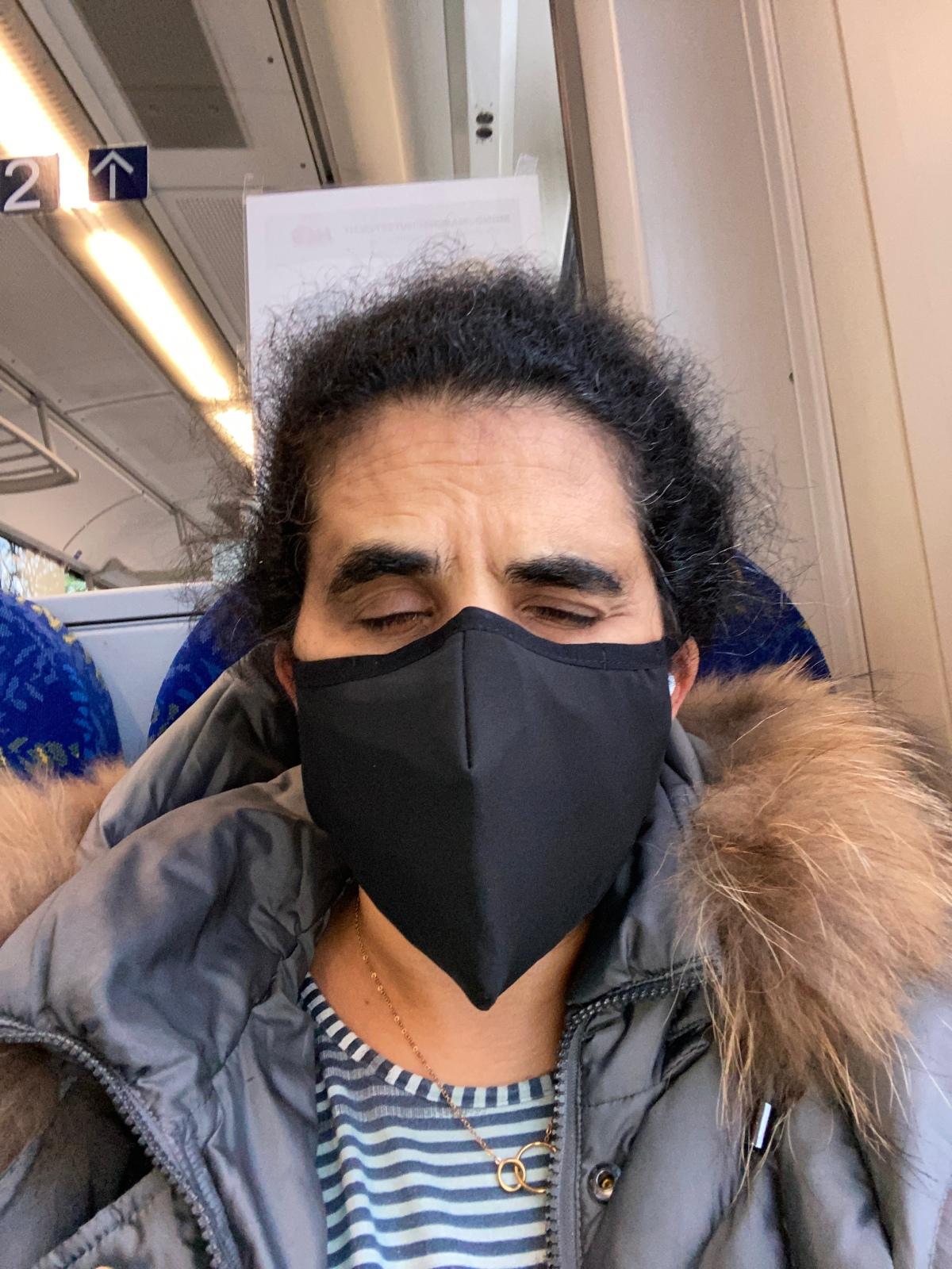 Lydia im Zug mit schwarzem Mundnasenschutz.
