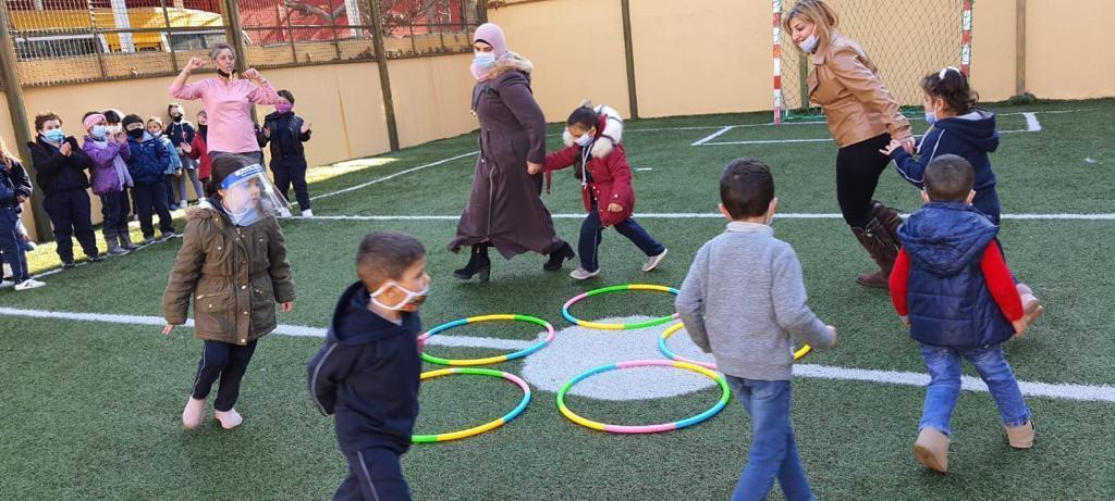 Mehrere Kinder laufen auf einem Schulhof, von denen zwei blinde Kinder geführt werden.