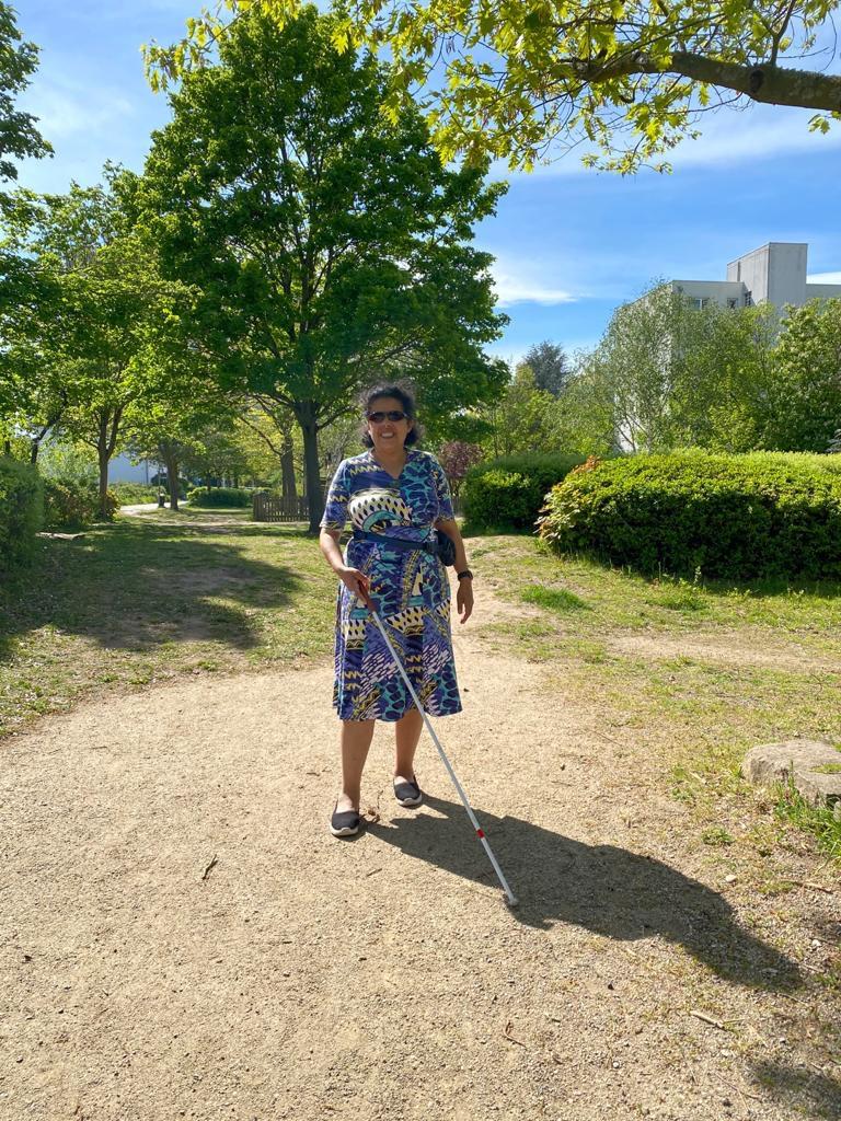 Lydia im Bunten Sommerkleid läuft mit Blindenstock einen Parkweg entlang.